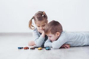 crianças usando aparelhos digitais em casa. irmão e irmã de pijama assistem desenhos animados e jogam em seu tablet de tecnologia foto