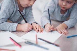 crianças deitam-se no chão de pijama e desenham a lápis. criança bonita pintando por pencils.hand de criança menina e menino desenhar e pintar com giz de cera. vista de perto foto