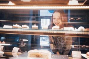 mulher sorridente para a câmera através da vitrine com doces e bolos no interior de um café moderno foto