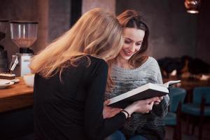 duas garotas absortas na leitura de um livro durante o intervalo no café. lindas mulheres jovens estão lendo um livro e tomando café foto