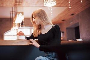mulher sorridente no café usando telefone celular e mensagens de texto nas redes sociais, sentada sozinha foto