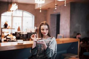 mulher jovem sorridente feliz usando telefone em um café. linda garota nas cores da moda da primavera foto