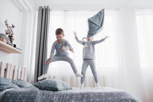 crianças em pijamas macios e quentinhos brincando na cama foto