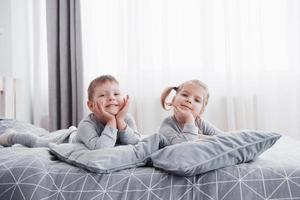 crianças felizes brincando no quarto branco. menino e menina, irmão e irmã brincam na cama de pijama. interior do berçário para crianças. pijamas e roupas de cama para bebês e crianças pequenas. familia em casa foto