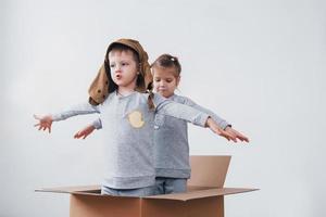 infância lúdica. garotinho se divertindo com a caixa de papelão. menino fingindo ser piloto. menino e menina se divertindo em casa foto