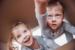 dois, um menino e uma menina abrindo uma caixa de papelão e subindo no meio dela. crianças se divertem foto