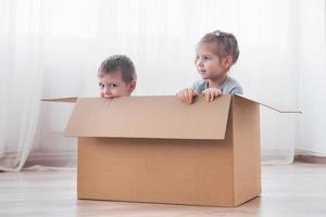 dois filhos, menino e menina, acabaram de se mudar para uma nova casa. foto do conceito ... as crianças se divertem.