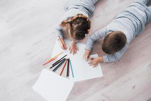 crianças deitam-se no chão de pijama e desenham a lápis. criança bonita pintando a lápis. foto