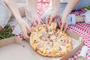 jovem casal fazendo piquenique comendo pizza foto