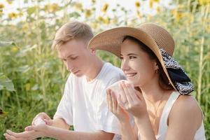 jovem casal fazendo piquenique no campo de girassol ao pôr do sol, limpando as mãos e o rosto foto