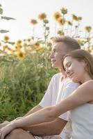 casal jovem fazendo piquenique no campo de girassol ao pôr do sol, mulher deitada no ombro do namorado foto