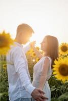 lindo casal se divertindo e dançando em campos de girassóis foto