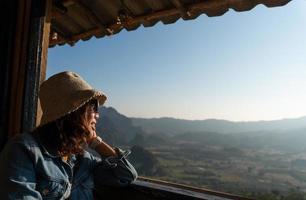 jovem mulher asiática sentada no quarto do hotel perto da janela, olhando a vista da montanha e beber café da manhã. turismo e conceito de férias foto