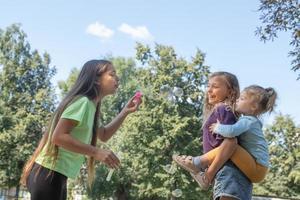 meninas brincam do lado de fora com bolhas de sabão. infância e conceito divertido foto