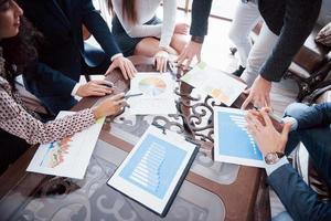 brainstorming da equipe de negócios. pesquisa de plano de marketing. papelada na mesa, laptop e celular foto