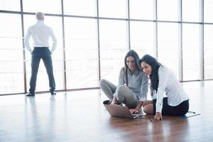jovens criativos em um escritório moderno. grupo de jovens empresários está trabalhando junto com o laptop. freelancers sentados no chão. cooperação realização corporativa. conceito de trabalho em equipe foto