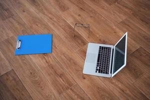 laptop óculos tablet no chão parquete fundo de madeira largo foto