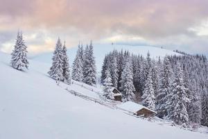 majestoso pôr do sol na pequena aldeia em uma colina nevada sob a Ucrânia. aldeias nas montanhas no inverno. bela paisagem de inverno. cárpatos, ucrânia, europa foto