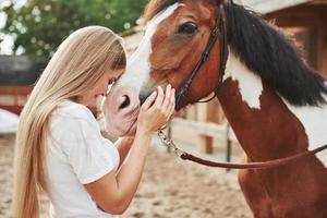 amo animais. mulher feliz com seu cavalo no rancho durante o dia foto