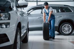 veias nas mãos. mecânico segurando um pneu na oficina. substituição de pneus de inverno e verão foto
