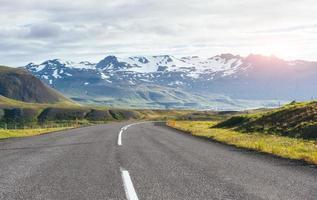 viajar para a Islândia. estrada em uma paisagem montanhosa ensolarada. Vulcão Vatna coberto de neve e gelo no fundo foto