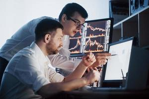 equipe de corretores está conversando em um escritório escuro com telas de exibição. analisar dados, gráficos e relatórios para fins de investimento. traders criativos em equipe foto