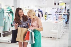lindas garotas segurando sacolas de compras, usando um telefone inteligente e sorrindo enquanto estão em um shopping center foto