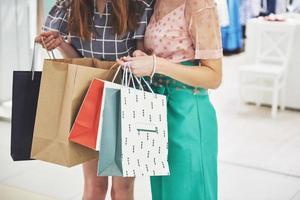 mulheres andando com sacolas enquanto fazem compras no shopping foto