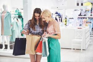 ótimo dia para fazer compras. duas lindas mulheres com sacolas de compras olhando uma para a outra com um sorriso enquanto caminhavam na loja de roupas foto