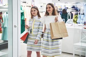 devemos olhar para os vestidos novos retrovisores de duas lindas mulheres com sacolas de compras desviando o olhar com um sorriso enquanto caminhava na loja de roupas foto