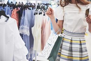 mulher nas compras. mulher feliz com sacolas de compras e cartão de crédito, desfrutando nas compras. consumismo, compras, conceito de estilo de vida foto
