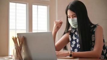 garota usando uma máscara com gestos confiantes. ela trabalha em casa para se proteger contra o vírus covid-19. foto
