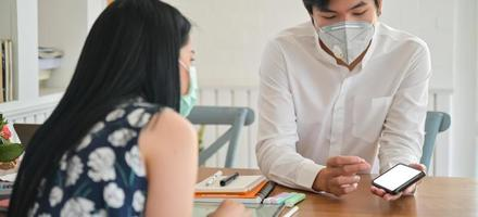 Agente de seguros masculino usando máscara está apresentando um pacote de seguro saúde contra coronavírus com um smartphone. foto