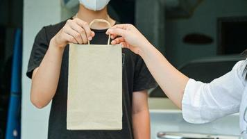 pedido em mãos produtos e alimentos entregues em casa para prevenir a transmissão do vírus corona ou kovid-19. foto
