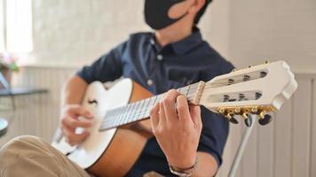 um jovem usando uma máscara tocando violão em casa, ficar em casa, trabalhar em casa. foto