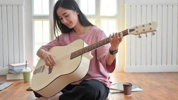 foto cortada de uma adolescente tocando guitarra enquanto ficava em casa enquanto colocava o vírus covid-19 em quarentena.