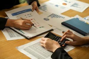 as empresárias da equipe usam caneta, calculadora estão planejando um plano de marketing para melhorar a qualidade do trabalho. foto
