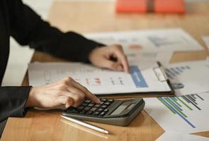 mulheres empresárias usam calculadora, caneta para planejar um plano de marketing para melhorar a qualidade. foto