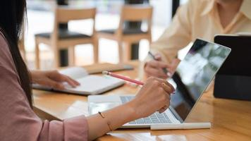 dois profissionais do sexo masculino e feminino planejam apresentar um novo projeto no futuro. com um laptop e acessórios de mesa. foto