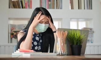 foto recortada de mulheres jovens e laptop trabalhando em casa, ela está estressada com o surto de coronavírus.