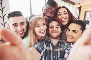 auto-retrato da unidade de raça mista de amigos africanos, americanos, asiáticos, caucasianos, homens barbudos felizes e belas mulheres com chapéu de Papai Noel vermelho mostrando o polegar para cima, tipo, gesto de ok para a câmera no escritório foto