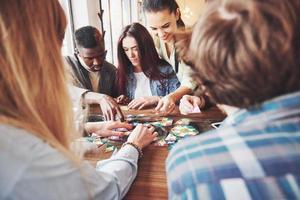 grupo de amigos multiétnicos criativos, sentados à mesa de madeira. pessoas se divertindo jogando jogo de tabuleiro foto