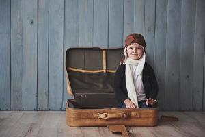 criança feliz no chapéu de piloto, brincando com a mala velha. infância. fantasia, imaginação. feriado foto