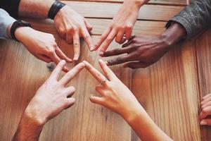close-up vista superior de jovens juntando as mãos. amigos fazendo uma forma de estrela com dedos mostrando união e trabalho em equipe foto