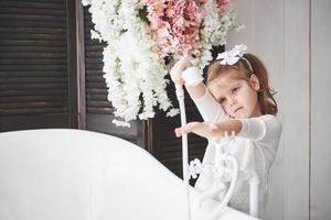 menina engraçada com cabelo encaracolado. prepare-se para tomar banho. banheiro espaçoso e iluminado. o conceito de um corpo saudável e limpo. cuidando de si mesmo desde a infância foto