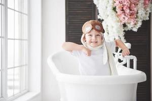 criança feliz com chapéu de piloto, jogando no banheiro. infância. fantasia, imaginação. foto