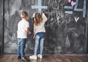 menina bonitinha e menino desenhando com giz de cera na parede. obras de criança. aluno fofo escrevendo no quadro-negro foto