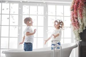 criança brincando com pétalas de rosa no banheiro de casa. menina e menino bajulando diversão e alegria juntos. o conceito de infância e a realização de sonhos, fantasia, imaginação foto
