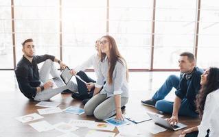 estratégia de planejamento em conjunto. equipe de negócios olhando papéis no chão com o gerente apontando para uma ideia. cooperação realização corporativa. planejamento desenho desenho. conceito de trabalho em equipe foto