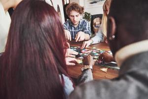 grupo de amigos criativos sentados à mesa de madeira. pessoas se divertindo jogando jogo de tabuleiro foto